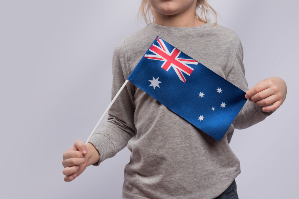 Child holds flag of Australia. Close up. Traveling with children in Australia.